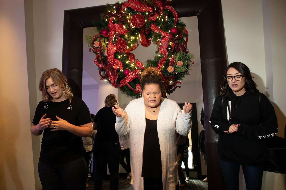 Dream Team members Rachel Clode, at left, Chanel Roland, and Alexia Ochoa, all of San Jose, pray during a huddle before CenterSet church services at Hotel Valencia Santana Row on Sunday, Dec. 9, 2018, in San Jose, Calif. Ali Roohi left behind a career in engineering to become a pastor in Silicon Valley.