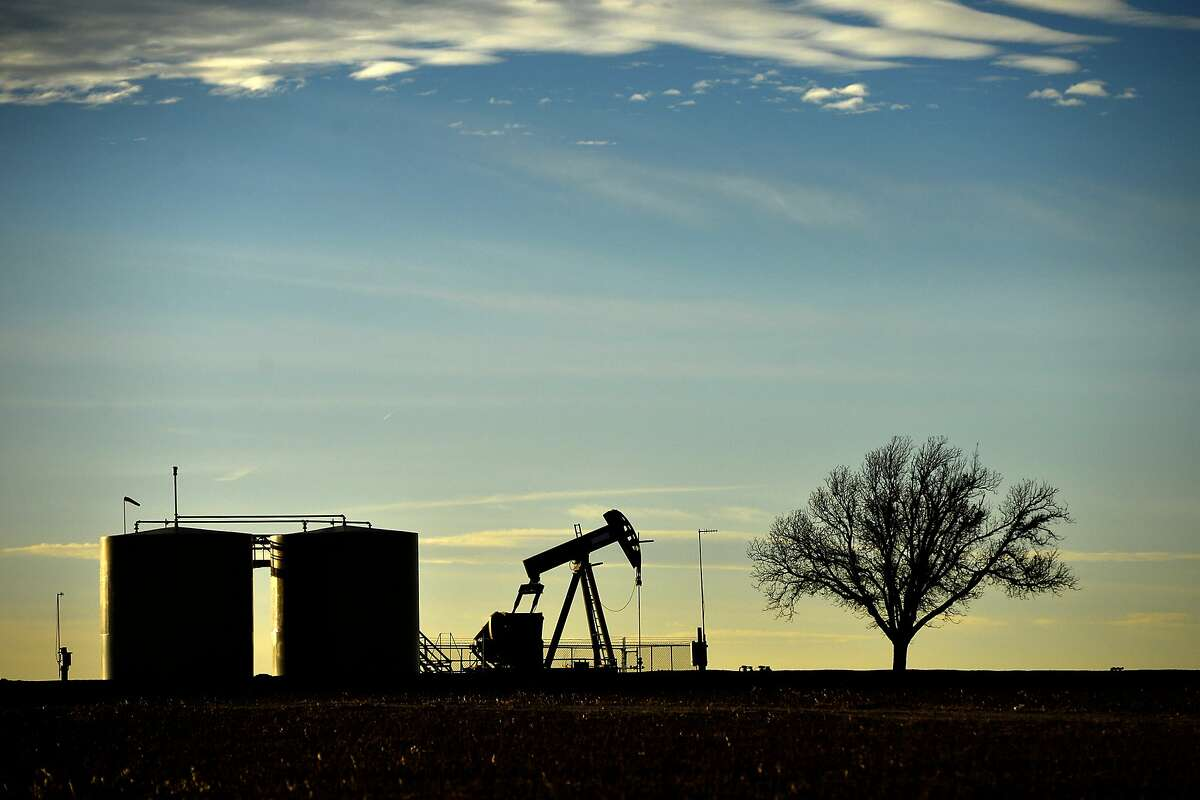 Pumpjack and tank battery operate in Greenwood, Midland County, Texas, Friday, Dec. 21, 2018.