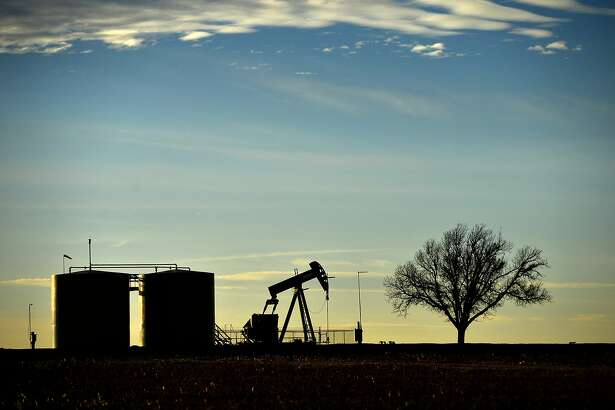 Pumpjack and tank battery operate in Greenwood, Midland County, Texas, Friday, Dec. 21, 2018. (James Durbin/Reporter-Telegram via AP)