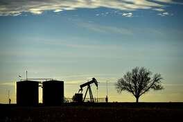 Pumpjack and tank battery operate in Greenwood, Midland County, Texas, Friday, Dec. 21, 2018. (James Durbin/Reporter-Telegram via AP)