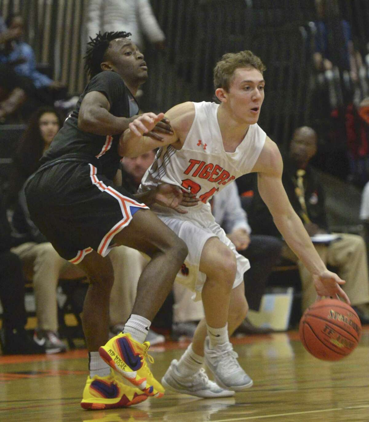 Ridgefield's James St. Pierre, right, drives by Stamford's Tyheim Burgess in Friday's game at Ridgefield High School.