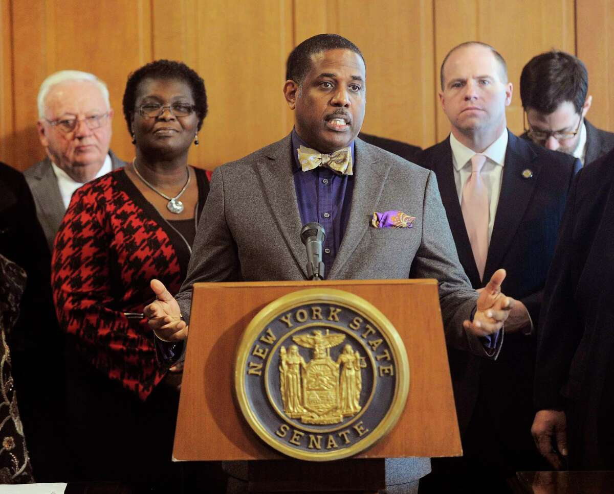 FILE- In this Feb. 6, 2017, file photo, Sen. Kevin Parker, D- Brooklyn, stands at the podium, flanked by Senate members during a news conference at the Capitol in Albany, N.Y. Parker wants to require police to scrutinize social media activity and online searches of handgun license applicants, and disqualify those who make violent or hateful posts. The bill's fate is uncertain amid questions from free-speech advocates. (AP Photo/Hans Pennink, File)