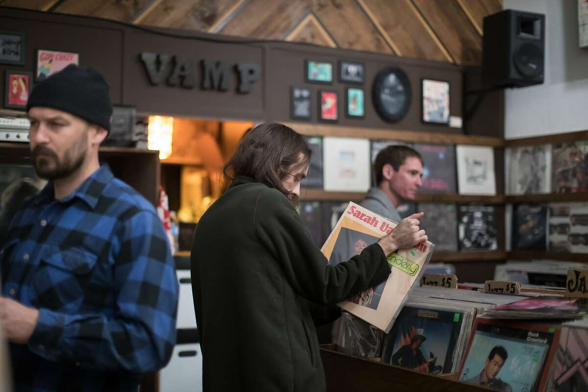 Dylan Allard holds an album he likes as he flips through others at VAMP on Saturday, Dec. 15, 2018, in Oakland, Calif.