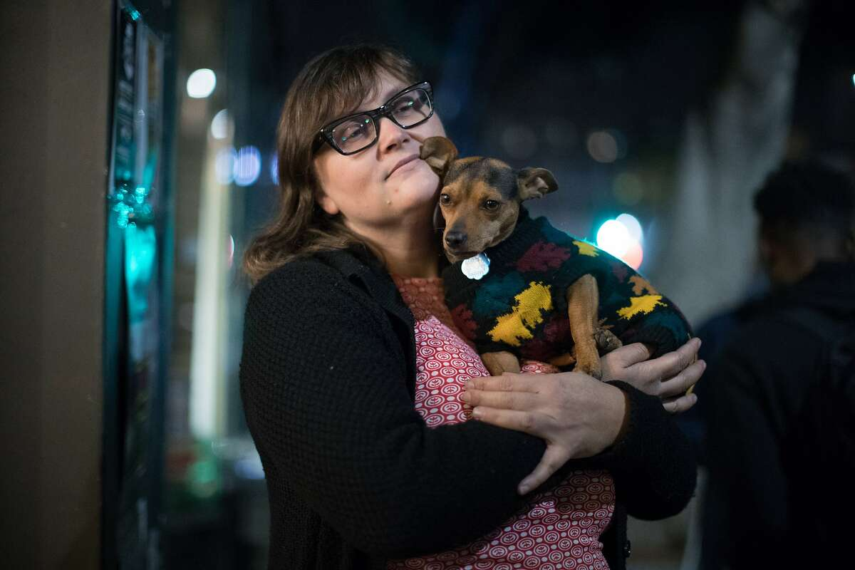 Tracy Parker holds her dog, Maxine Brown, 4, outside her store she owns with Fernando Carpenter, VAMP on Saturday, Dec. 15, 2018, in Oakland, Calif.