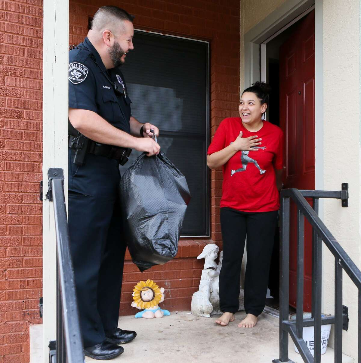 Edgewood ISD police officer Rene Ramirez delivers Christmas presents to Frances Morales' six children on Wednesday, Dec. 19, 2018. For the fourth consecutive year, the Edgewood ISD police department is delivering presents to more than 200 children in the school district, identified by officers, counselors and teachers, that might not otherwise receive presents.