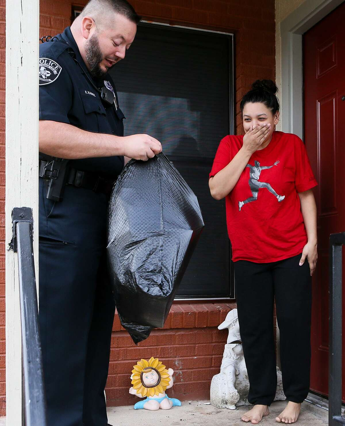 Frances Morales reacts as Edgewood ISD police officer Rene Ramirez begins to deliver Christmas presents to her six children on Wednesday, Dec. 19, 2018. For the fourth consecutive year, the Edgewood ISD police department is delivering presents to over 200 children in the school district, identified by officers, counselors and teachers, that might not otherwise receive presents.