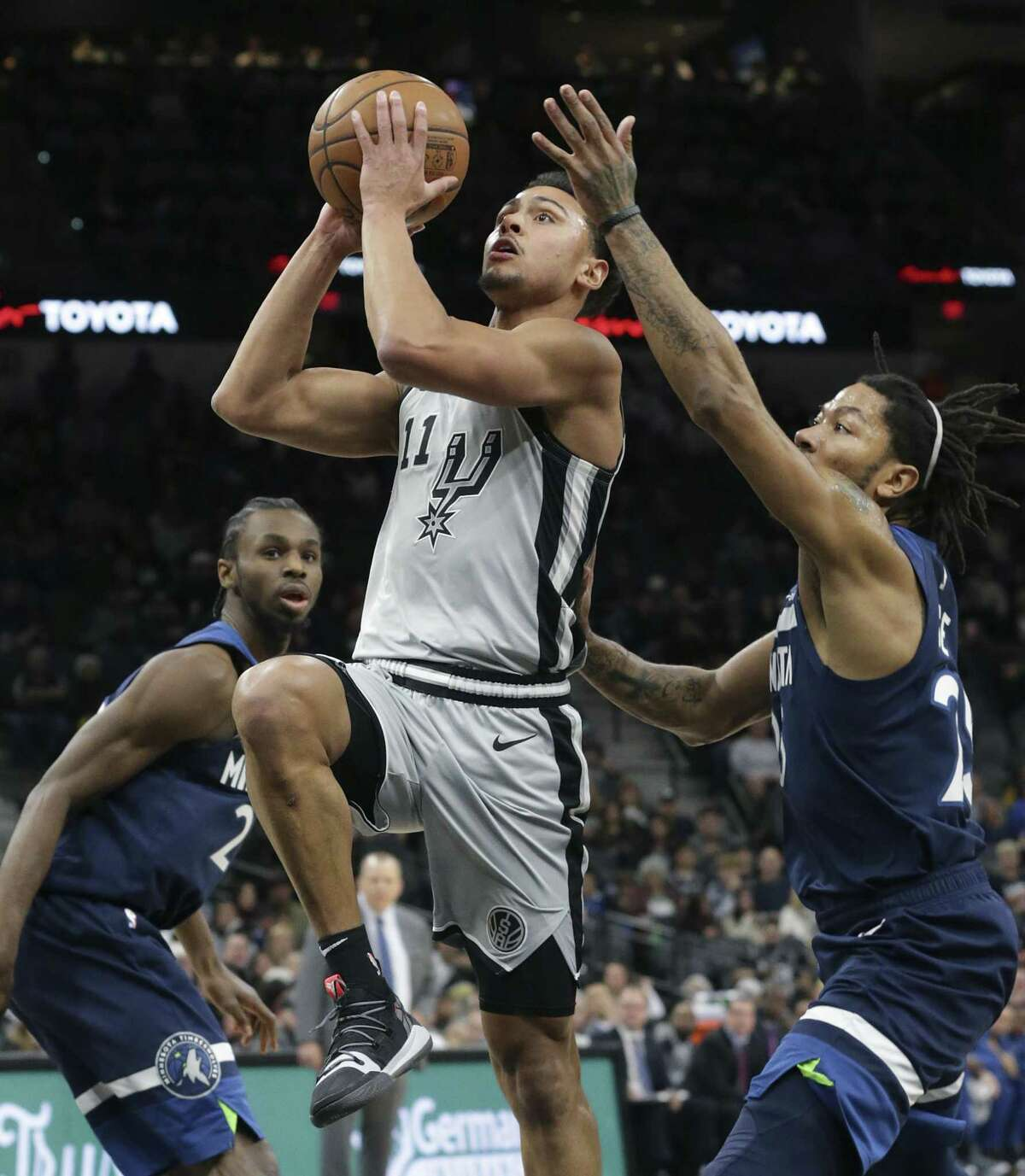 Bryn Forbes slips by Wolves defenders Andrew Wiggins, left, and Derrick Rose to get to the hoop as the Spurs host the Timberwolves at the AT&T Center on December 21, 2018.