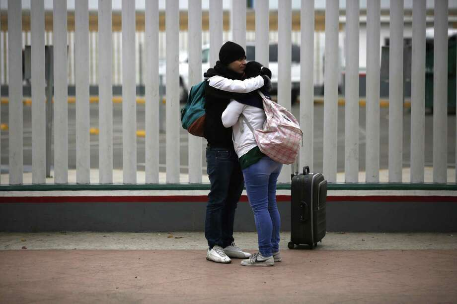 Un par de migrantes se abrazan después de recibir uno de los 50 turnos para solicitar asilo en EU, en Tijuana, México, el viernes. Photo: Moisés Castillo /Associated Press / Copyright 2018 The Associated Press. All rights reserved