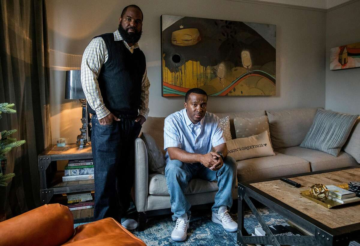 Shadeed Wallace-Stepter (right) and Earlonne Woods pose for a portrait in the living room of Re:Store Justice in Oakland, Calif. Thursday, Dec. 20, 2018.
