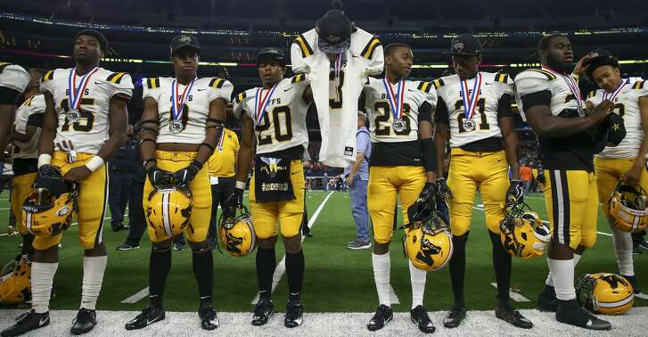 Fort Bend Marshall players hold Drew Conley's jersey as they were presented with their second place medals after losing 55-19 to Aledo in the 5A Division 2 championship game at AT&T Stadium Friday, Dec. 21, 2018, in Dallas.