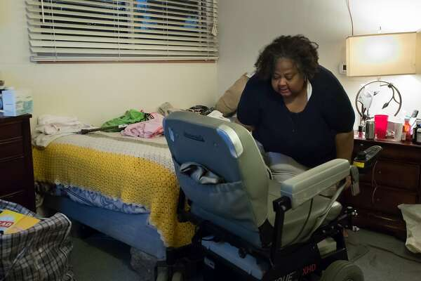 Lisa Johnson gets onto her motorized wheelchair in her childhood home on Tuesday, Dec. 18, 2018, in Hayward, Calif.