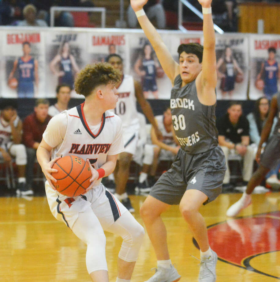 Plainview sophomore guard Austin Hauk looks to pass the ball with Lubbock High senior guard Phillip Martinez guarding during the District 3-5A boys basketball game on Friday night in Plainview. Photo: Alexis Cubit/Plainview Herald