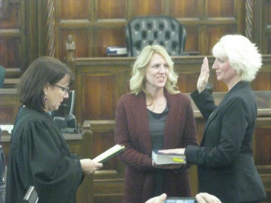 Judge Dorene Allen, far left, swears in state Rep. Annette Glenn, far right, as Karann Chew looks on Friday at the Midland County Courthouse. (Mitchell Kukulka/For the Daily News)