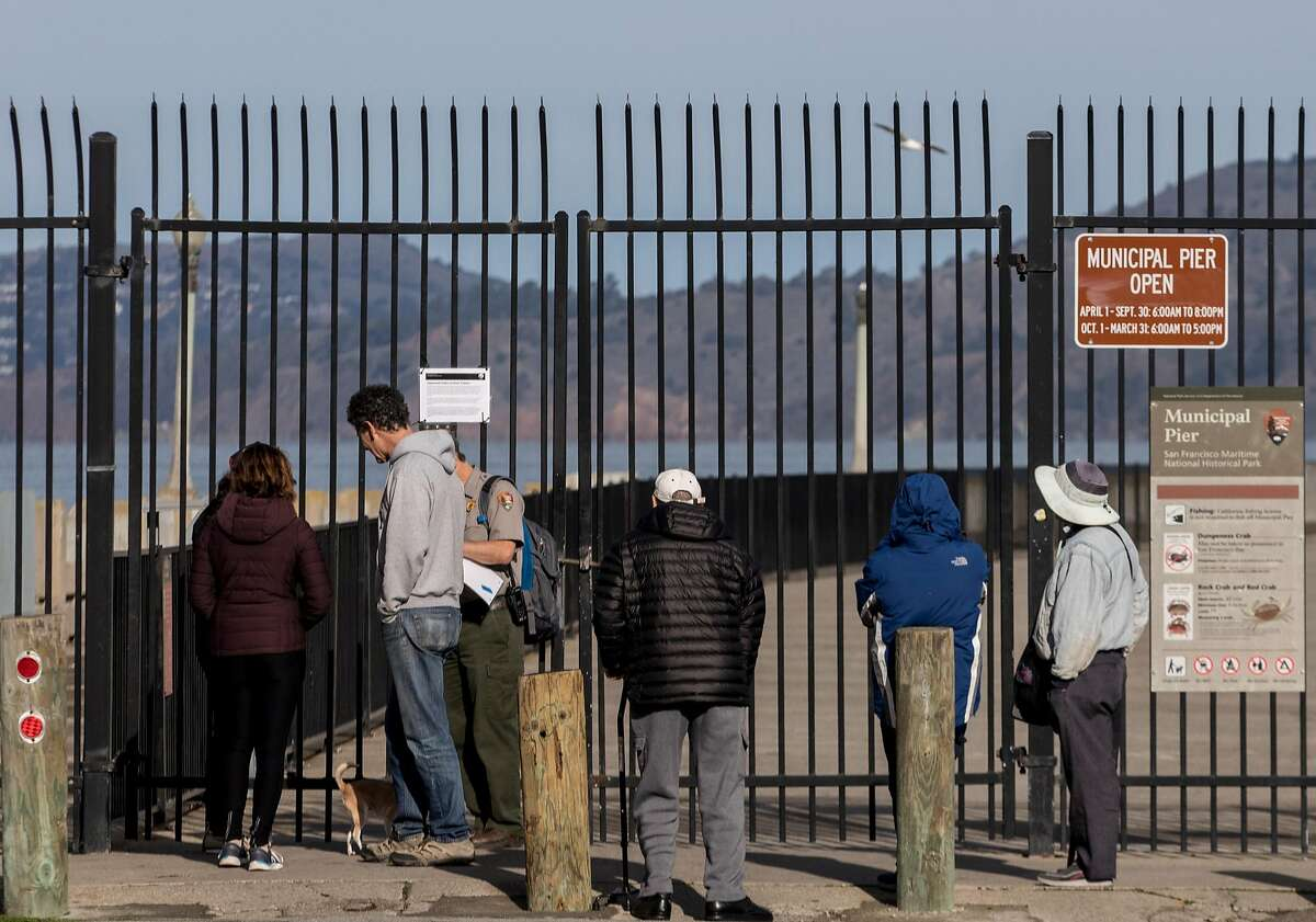 A handful of tourists and fisherman gather around Aquatic Park Pier as officials lock its gates as the result of a partial government shutdown at the San Francisco Maritime National Park in San Francisco, Calif. Saturday, Dec. 22, 2018.
