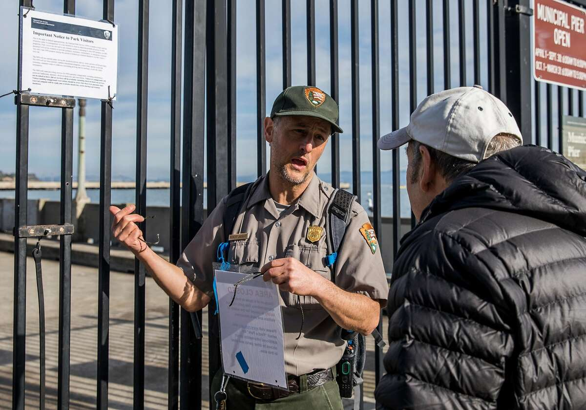 A National Parks employee who wished not to be named explains the closure of Aquatic Park Pier as the result of a partial government shutdown at the San Francisco Maritime National Park in San Francisco, Calif. Saturday, Dec. 22, 2018.