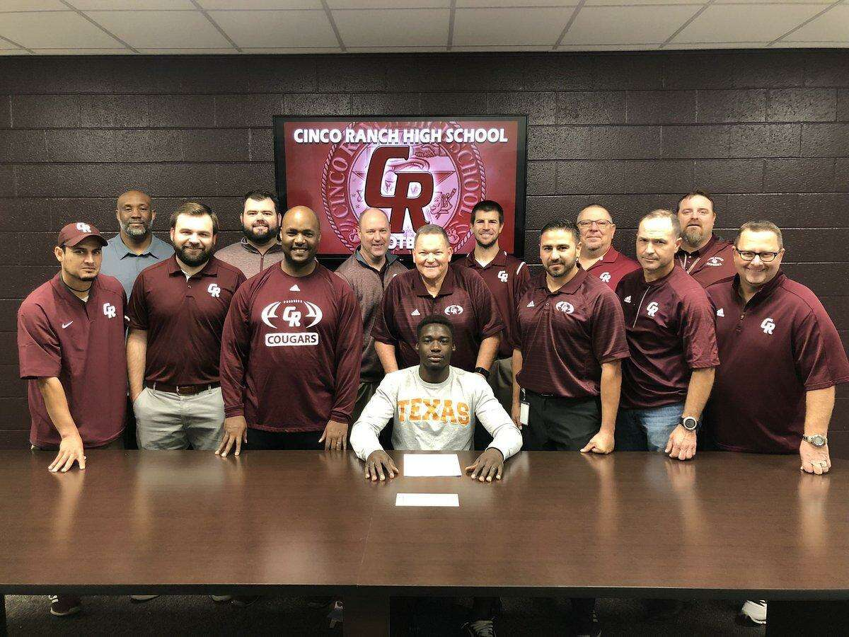 Cinco Ranch High School senior David Gbenda celebrates with the Cougars coaching staff after signing his National Letter of Intent to attend and play football at the University of Oklahoma.
