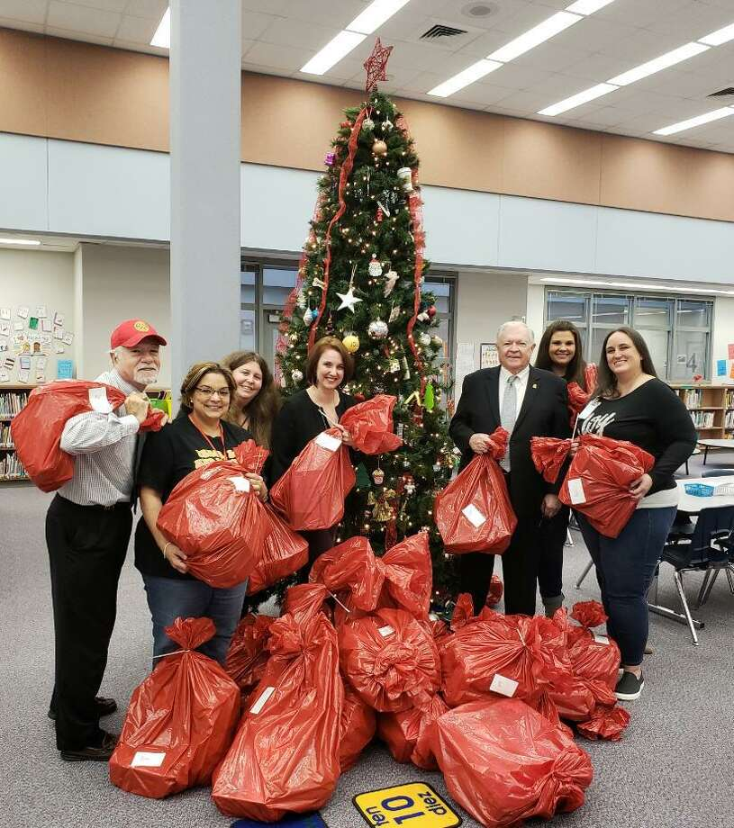 Members of Rotary Club of Katy served as Santa helpers on Dec. 17 delivering gifts to 119 students at Hutsell, Sundown and Rhoads Elementary schools. Above, from left, at Rhoads Elementary are David Frishman, Rotarian; Jackie Belmarez, instructional coach math and science; Kathryn Johnson, campus counselor; Emily Chambers, instructional coach reading and language arts; Ken Burton, Rotarian; Jillian Wilke, assistant principal; and Kara Fox, assistant principal. Photo: Courtesy Rotary Club Of Katy / Courtesy Rotary Club Of Katy
