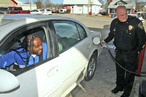 Alton Police Chief Jake Simmons pumps free gas fior Donald McCrady, of Alton, Saturday at Hit-N-Run on State Street during a gasoline giveaway, coordinated by Mustache March 4PD and the owners of Hit-N-Run. It took little more than an hour for 150 drivers to collect their complimentary $10 worth of fuel.