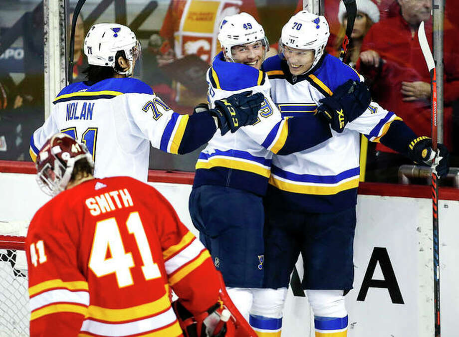 The Blues' Oskar Sundqvist, right, celebrates a goal with teammates Ivan Barbashev, center, and Jordan Nolan, left, as Calgary Flames goalie Mike Smith looks away in the third period of Saturday's games in Calgary, Alberta. Photo: AP Photo