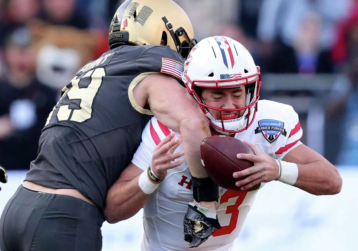 UH freshman quarterback Clayton Tune, right, coughs up the football after a crunching blow by Army's James Nachtigal.