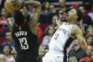 San Antonio Spurs guard Bryn Forbes (11) fouls on Houston Rockets guard James Harden (13) during the first quarter of the NBA game at Toyota Center on Saturday, Dec. 22, 2018, in Houston.