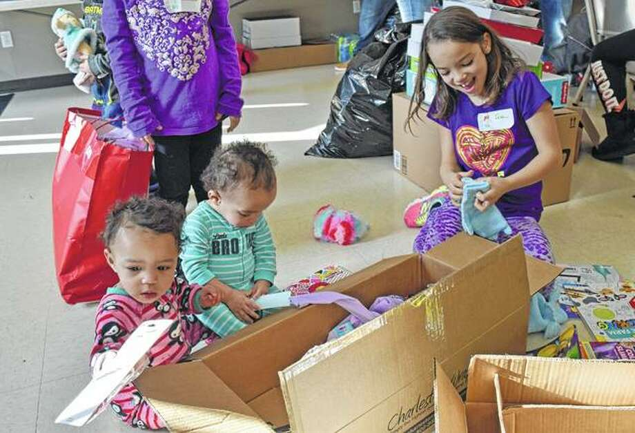 Twin sisters Houston and Tennessee, both 1, and their sister Ada, 8, enjoy their new Christmas presents such as slime, colored pencils, and mittens at the charity event Saturday hosted by Cricket Wireless and its authorized retail partner Freedom Wireless at First Christian Church.