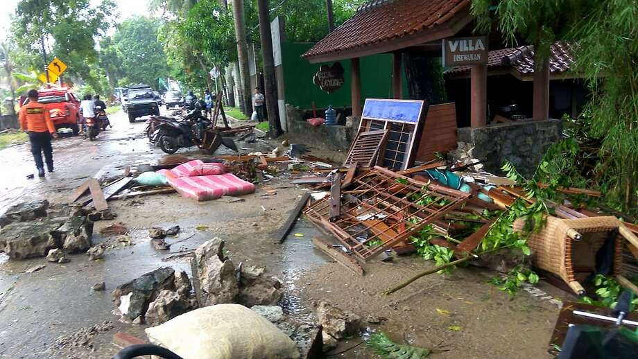 Debris from damaged buildings clutters a street after a tsunami in Carita, Indonesia. Photo: Ronald / AFP / Getty Images