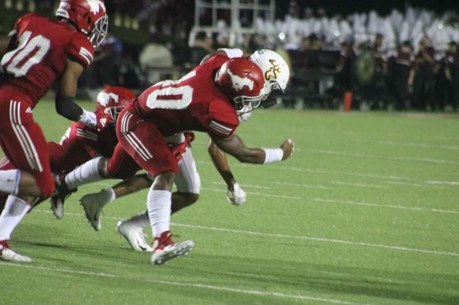 A member of the newly-crowned state champion North Shore Mustangs brings down a Deer Park ballcarrier during their Oct. 12th game. Saturday night in Dallas, the District 21-6A champions defeated Duncanville 41-36 to claim the Division I state crown, completing a 16-0 record. Photo: Robert Avery