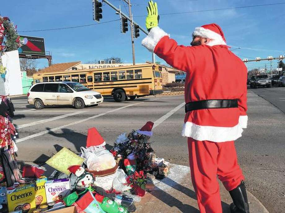 Jimmy Izbinski, wearing a Santa suit, waves to motorists passing the Christmas weed on Tuesday in Toledo, Ohio. The street corner weed decked out with lights and ornaments is spreading holiday goodwill. Photo: John Seewer | Associated Press