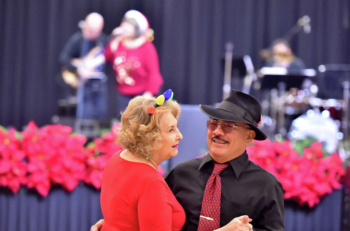 Alfonso Varela and Edna Gonzales dance during the HEB Feast of Sharing Holiday Dinner at the Henry B. Gonzalez Convention Center Saturday. HEB officials estimated that they would feed 10,000-12,000 people at the event.