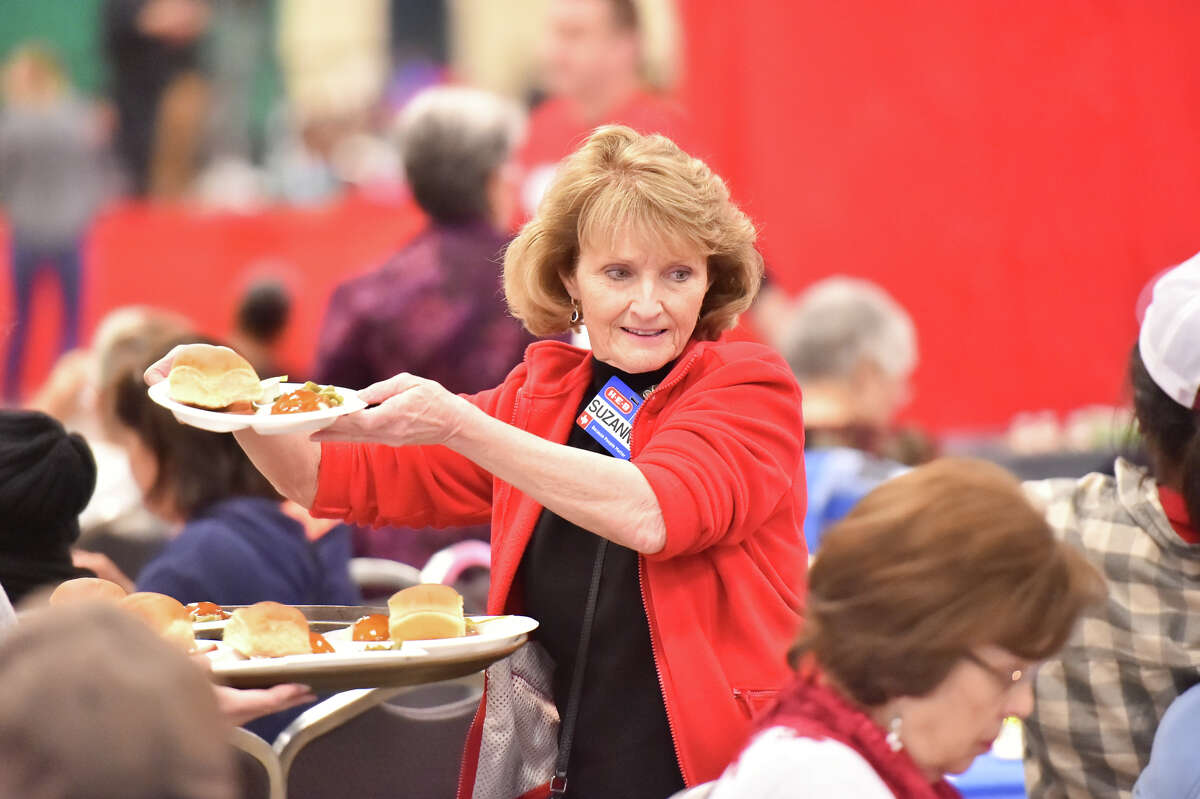 Suzanne Wade serves guests during the HEB Feast of Sharing Holiday Dinner at the Henry B. Gonzalez Convention Center Saturday. HEB officials estimated that they would feed 10,000-12,000 people at the event.