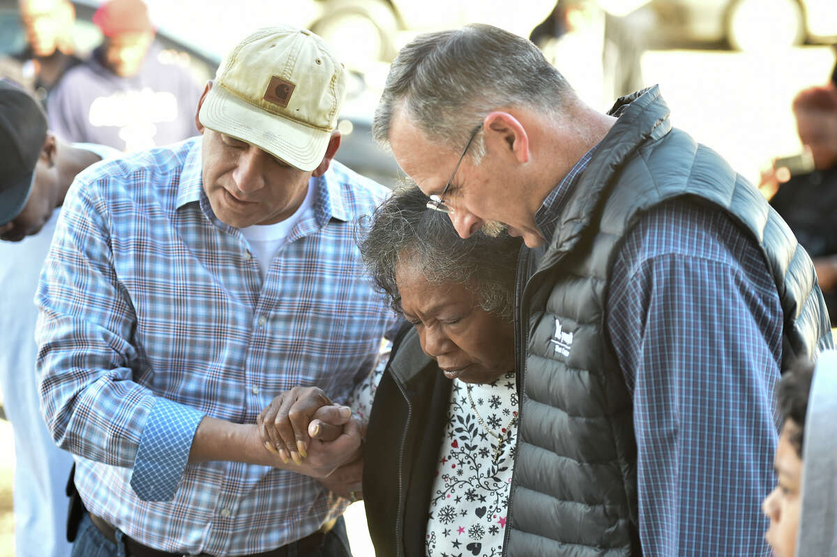 Mary Cole prays with neighbors Fernando Trujillo and Ralph Gibson as she prepares to enter her new home that members of the community built to replace her West End home that suffered extensive damage in a fire.
