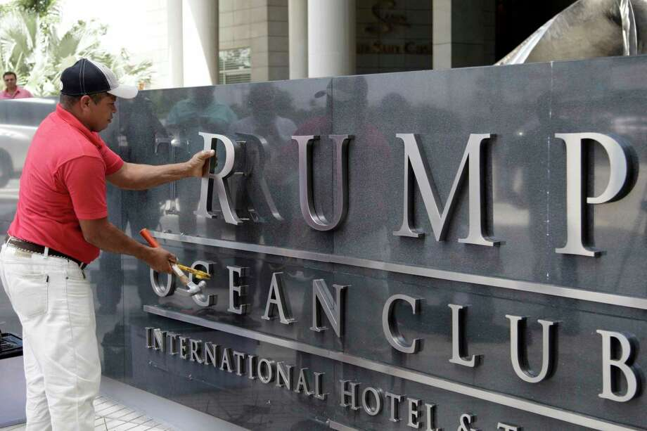 FILE - In this March 5, 2018 file photo, a man removes the word Trump, off a marquee outside the Trump Ocean Club International Hotel and Tower in Panama City. The luxury hotel that used to bear the Trump name has formally been rebranded to JW Marriott on Sept. 25, after a bitter dispute over control. Many believed that the presidency would be a boon to Donald Trump's business, but two years since he took office signs are mounting that it has hurt it instead. (AP Photo/Arnulfo Franco, File) Photo: Arnulfo Franco / Copyright 2018 The Associated Press. All rights reserved.