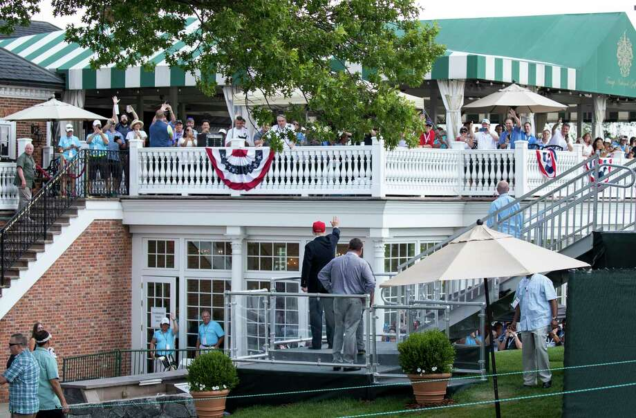 "In this July 15, 2017 file photo, President Donald Trump turns to wave to the people gathered at the clubhouse as his walks to his presidential viewing stand during the U.S. Women's Open Golf tournament at Trump National Golf Club in Bedminster, N.J. The president's divisive comments that are so popular with his political base, appear to have turned off the affluent who fuel his businesses. ""The people you see in the club now are whittled down to the loyalists, and the people who can't stand him are less and less there,"" says a member of his Bedminster, golf resort who requested anonymity so as not to alienate other members. (AP Photo/Carolyn Kaster, File) Photo: Carolyn Kaster / Copyright 2018 The Associated Press. All rights reserved."
