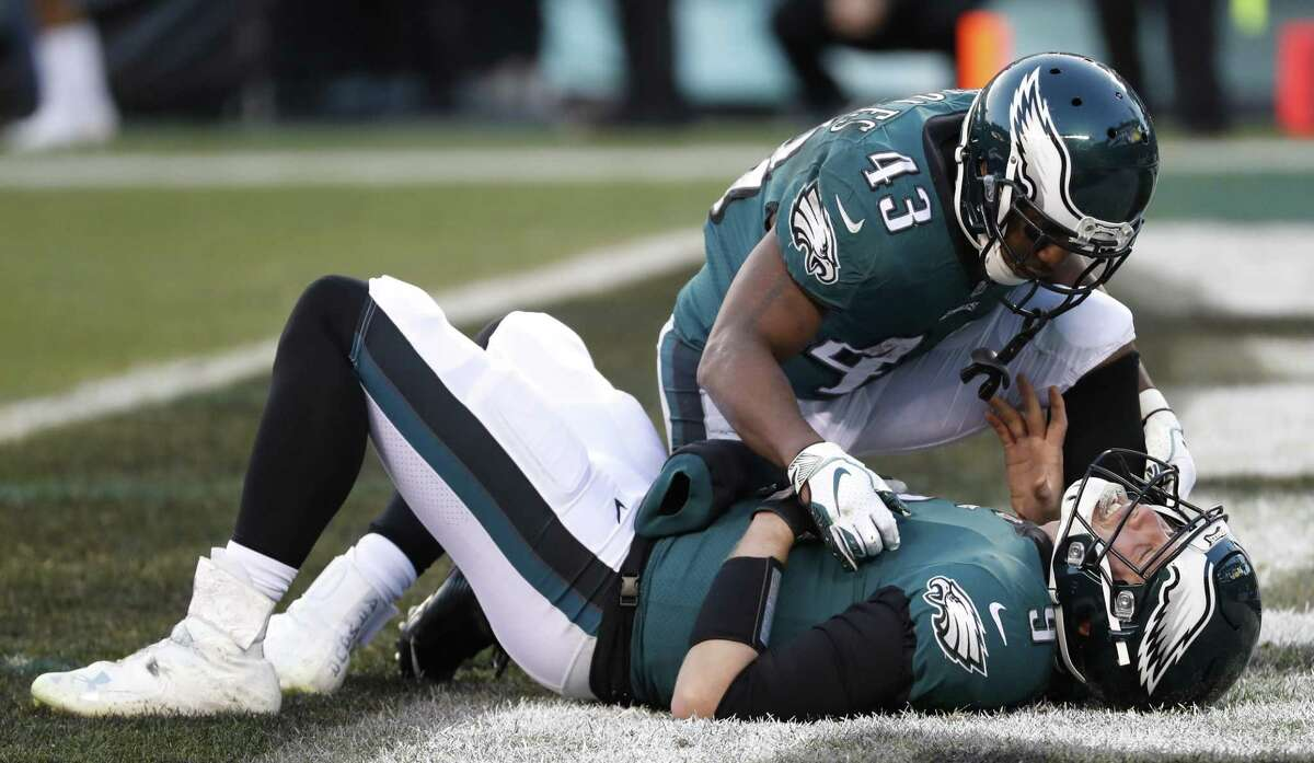 Philadelphia Eagles running back Darren Sproles (43) checks on quarterback Nick Foles (9) as he lies in the end zone after suffering an injury on a hit by Houston Texans outside linebacker Jadeveon Clowney during the fourth quarter of an NFL football game at Lincoln Financial Field on Sunday, Dec. 23, 2018, in Philadelphia. Foles sat out one play. Clowney was penalized for roughing the passer.