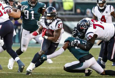 Houston Texans running back D'Onta Foreman (27) is tripped up by Philadelphia Eagles defensive back Tre Sullivan (37) as he runs up the middle during the third quarter of an NFL football game at Lincoln Financial Field on Sunday, Dec. 23, 2018, in Philadelphia.