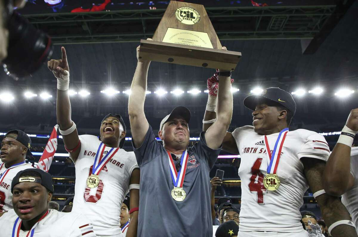 As his players cheer, North Shore coach Jon Kay hoists the state championship trophy and salutes the Mustangs' fans after Saturday night's wild 41-36 victory over Duncanville at AT&T Stadium in Arlington.
