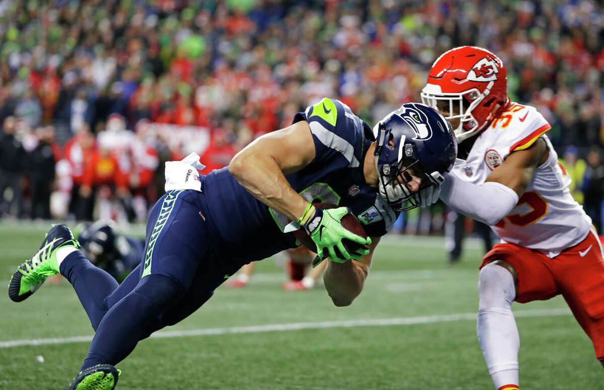 Seattle Seahawks tight end Nick Vannett, left, dives past Kansas City Chiefs cornerback Charvarius Ward, right, for a touchdown during the first half of an NFL football game, Sunday, Dec. 23, 2018, in Seattle. (AP Photo/Elaine Thompson)