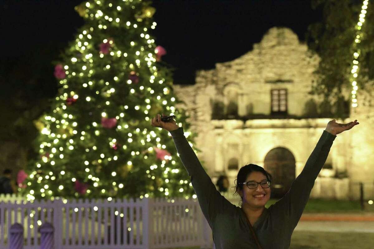 Cassandra Hernandez enjoys herself by Alamo Plaza on Thursday night, Dec. 20, 2018. The city's official Christmas tree is in Travis Park, not Alamo Plaza.