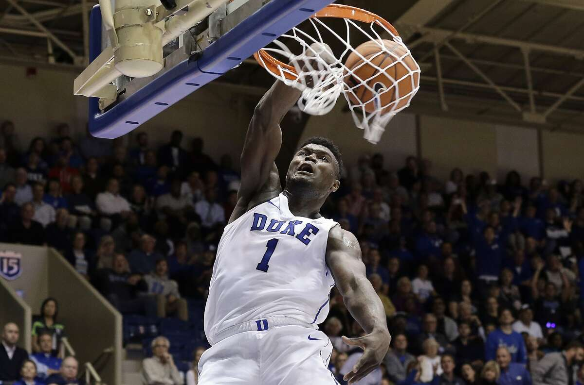 FILE - In this Nov. 14, 2018, file photo, Duke's Zion Williamson (1) dunks against Eastern Michigan during the second half of an NCAA college basketball game, in Durham, N.C. Williamson sure seems comfortable as the star of the show at No. 2 Duke. With his mix of high-flying acrobatics on the court and his charismatic personality off it, Williamson has emerged as the natural face of the Blue Devils _ and as college basketball as a whole. (AP Photo/Gerry Broome, File)