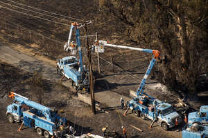 Pacific Gas & Electric Co. (PG&E) employees work to fix downed power lines burned by wildfires in Santa Rosa, Calif., on Oct. 12, 2017.
