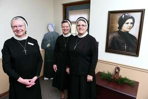 From left, Sister Sheila O'Neill, president of Sacred Heart Academy, Sister Colleen Therese Smith, director of mission advancement for the Apostles of the Sacred Heart of Jesus, and Sister Mariette Moan, provincial councilor for the order, are photographed near photos of Mother Clelia Merloni at the Provincial House on Benham Street in Hamden on Dec. 17.