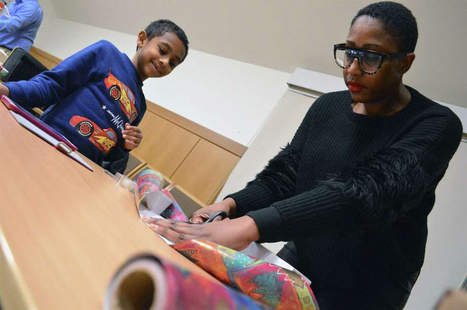 "Daniel Matos, 8, of Easton watches his mom, Shalenta Hardison wrapping presents at the ""Gift Wrap and Yap"" event at Darien Library, Thursday, Dec. 20, 2018, in Darien, Conn. Photo: Jarret Liotta / For Hearst Connecticut Media / Darien News Freelance"