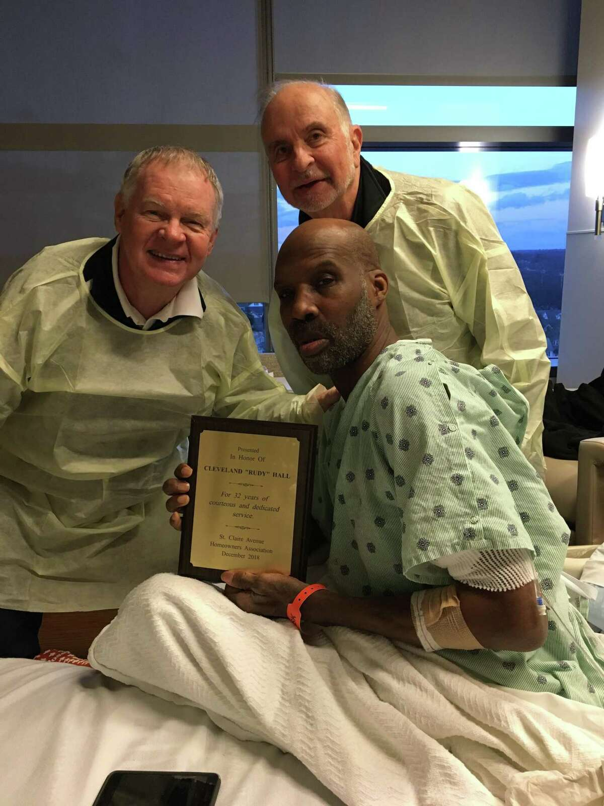 Cleveland 'Rudy' Hall is presented with a plaque commemorating his decades of service to the St. Claire Homeowners Association. He receives the award from Andy Reid the group's president, accompanied by Al Amato, after he was hospitalized for complications from diabetes.