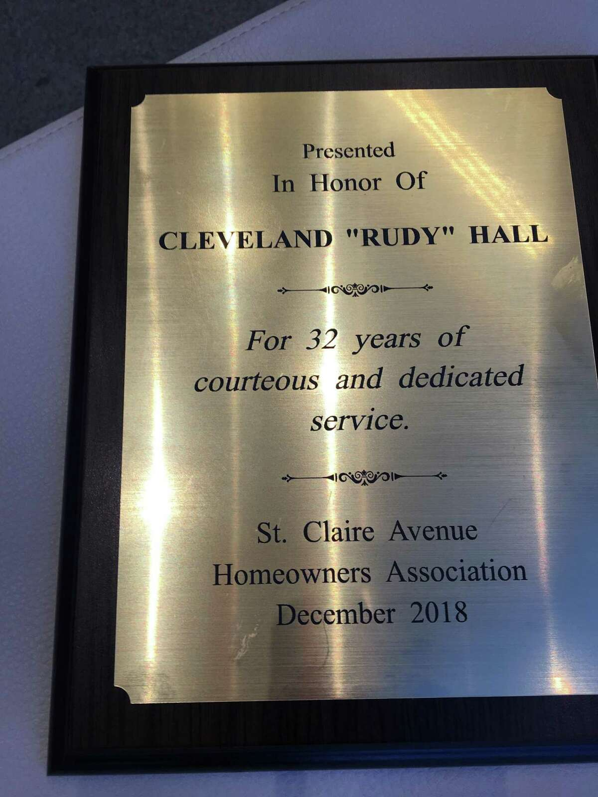 Cleveland 'Rudy' Hall is presented with a plaque commemorating his decades of service at the St. Claire Homeowners Association. He receives the award from Andy Reid the group's president, accompanied by Al Amato, after he was hospitalized for complications from diabetes.