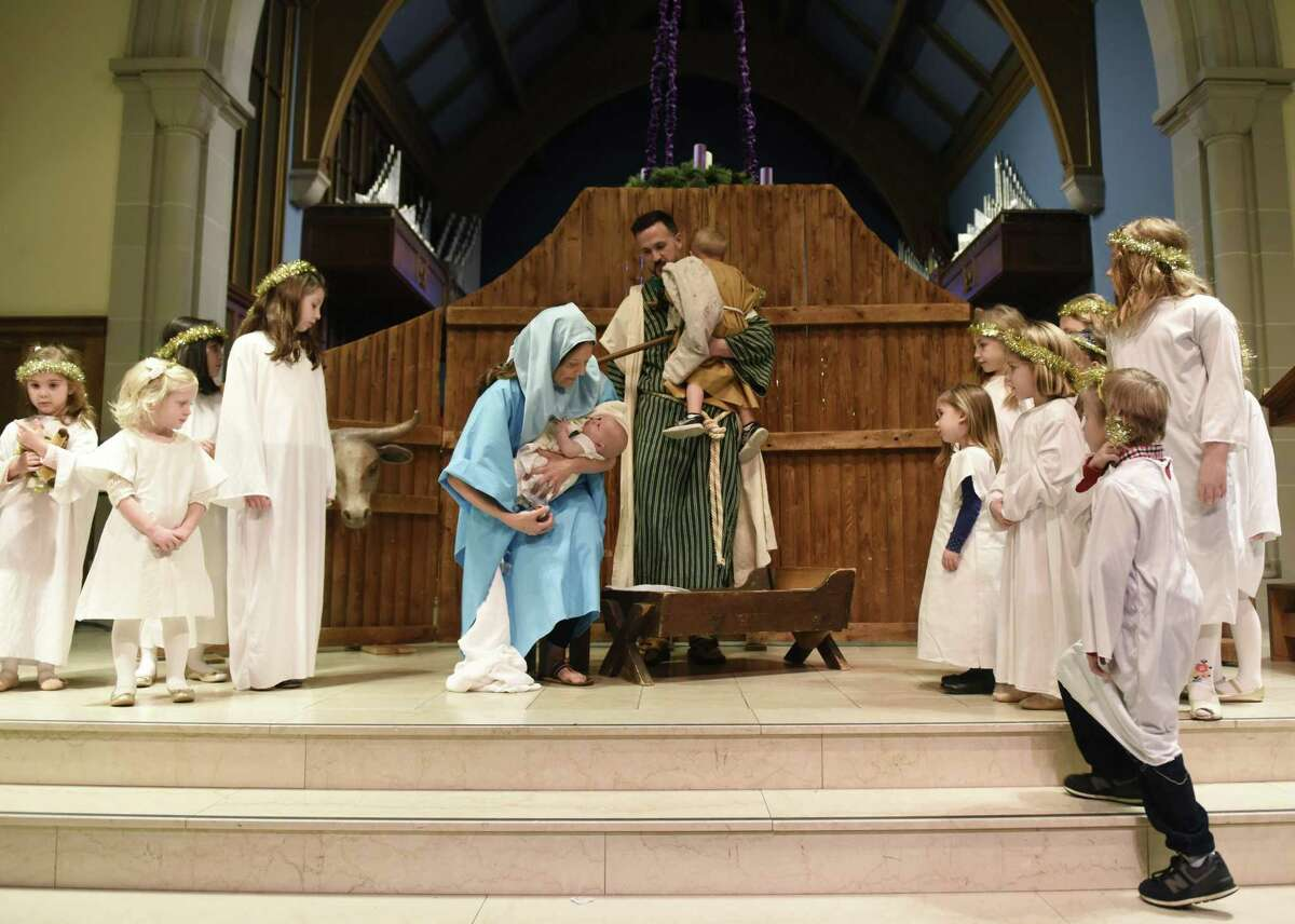 The Rev. Patrick Collins, his wife Kate, and children Jonah and Norah portray Joseph, Mary, Jesus and a shepherd as children, dressed as angels, surround them during a live nativity re-enactment at the Children's Christmas Eve Service at First Congregational Church of Greenwich in Old Greenwich, Conn. Monday, Dec. 24, 2018. The kids program featured a live nativity re-enactment, traditional Christmas carols, and lighting of the Christ candle.
