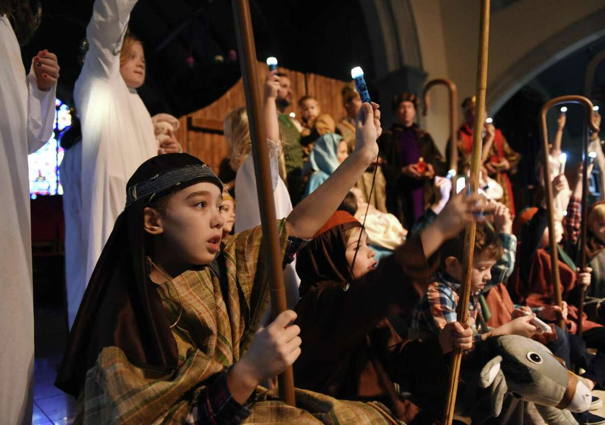 Sarah Bodenstein, 10, dresses as a shepherd while holding a light and singing