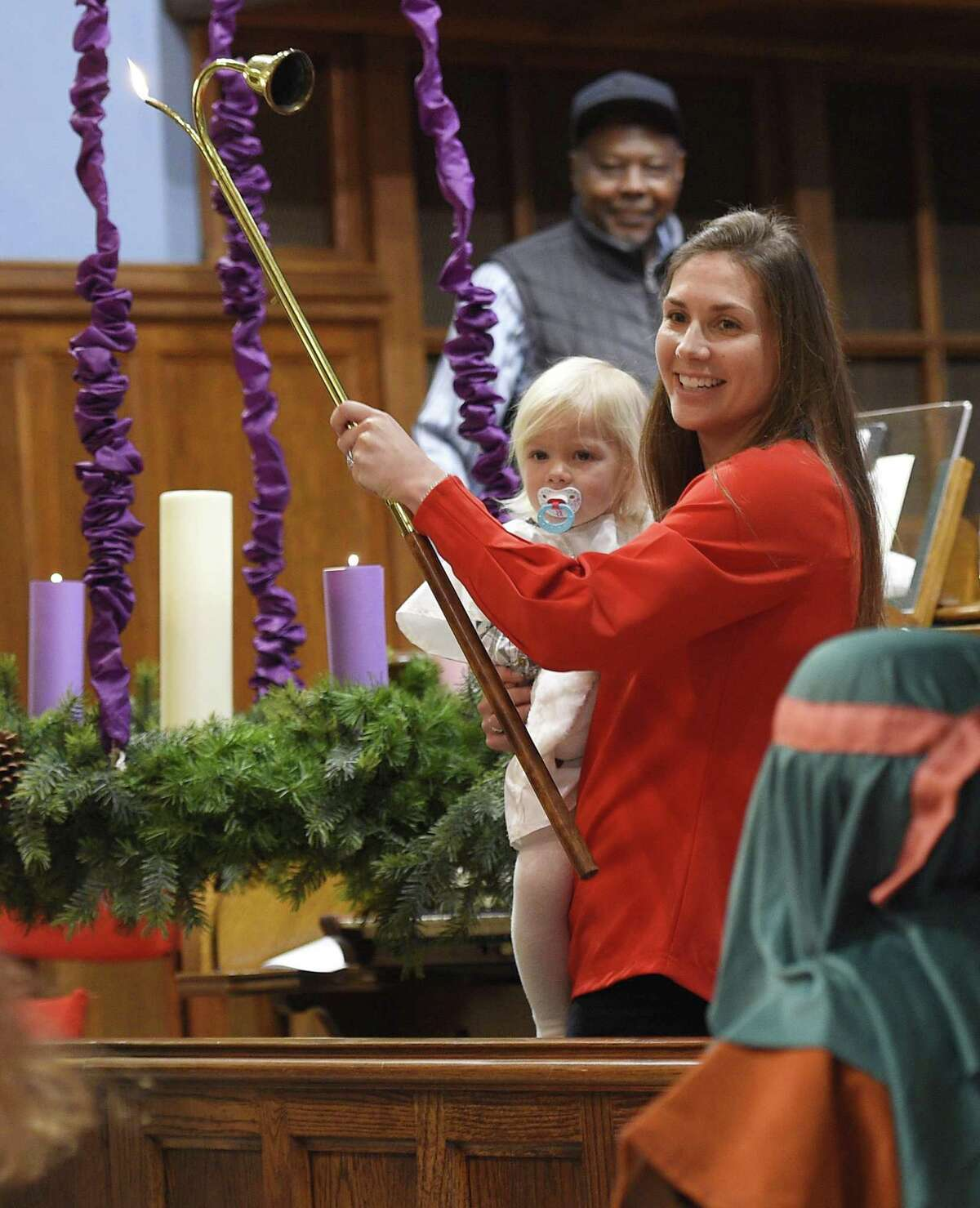 Sarah Sippel and her daughter, Remy, light the Christ candle during the Children's Christmas Eve Service at First Congregational Church of Greenwich in Old Greenwich, Conn. Monday, Dec. 24, 2018. The kids program featured a live nativity re-enactment, traditional Christmas carols, and lighting of the Christ candle.
