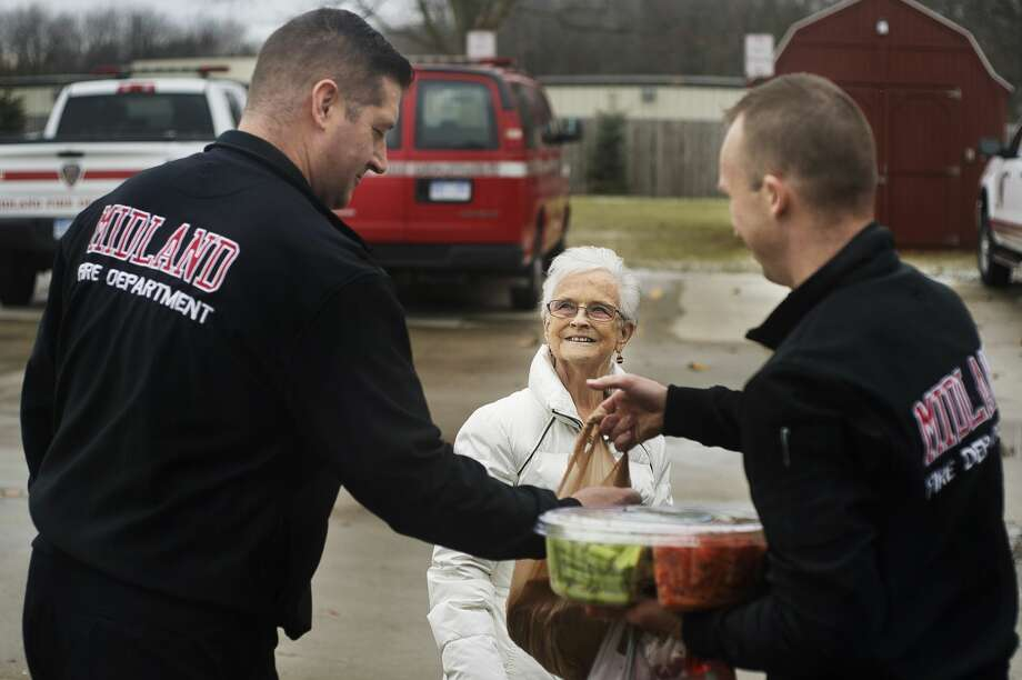 Dolores Davis, center, watches as Lieutenant Bob Arnold, left, and Phil Hepworth, right, of the Midland Fire Dept., carry a Christmas meal donated by Davis and other residents of Washington Woods senior housing into the fire station on Haley Street on Monday, Dec. 24, 2018 in Midland. (Katy Kildee/kkildee@mdn.net) Photo: (Katy Kildee/kkildee@mdn.net)