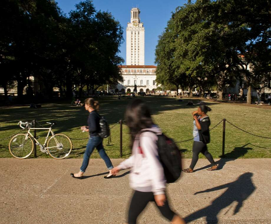 University of Texas students and faculty make thier way through campus via the UT Tower on Tues., Nov. 19, 2013 in Austin.